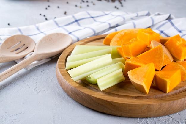 Abóbora fatiada em uma placa de madeira. comida caseira com abóbora. ainda vida na cozinha