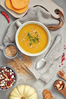 Abóbora, feijão misto e sopa de creme de batata doce em uma tigela de cerâmica, vista superior com ingredientes