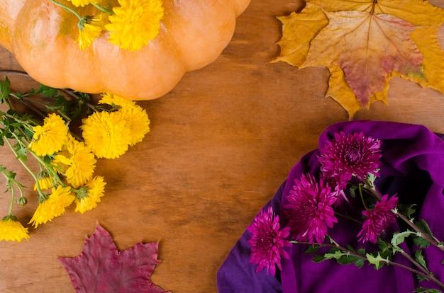 Abóbora, flores de crisântemo e folhas secas de outono