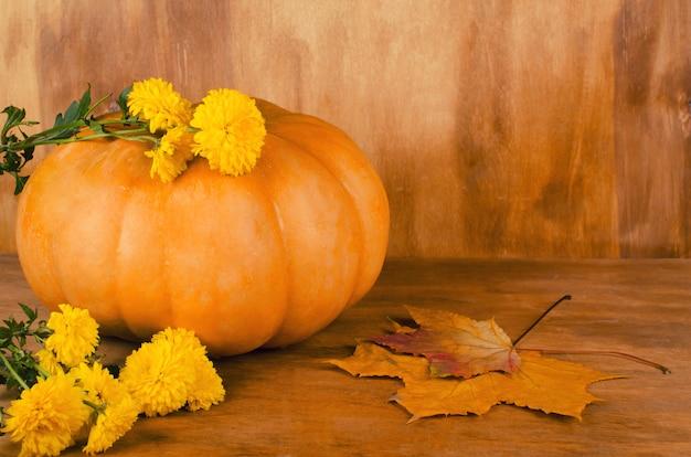 Abóbora, flores de outono e folhas em um fundo de madeira