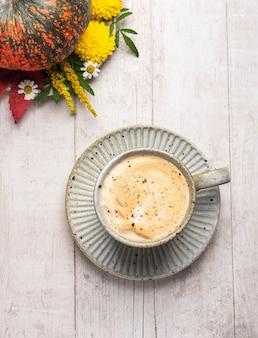 Abóbora, flores, folhas de outono e cappuccino