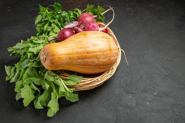 Abóbora fresca com rabanete e verduras em uma mesa de cor escura com alimentos maduros
