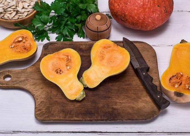 Abóbora fresca cortada ao meio em uma placa de cozinha de madeira