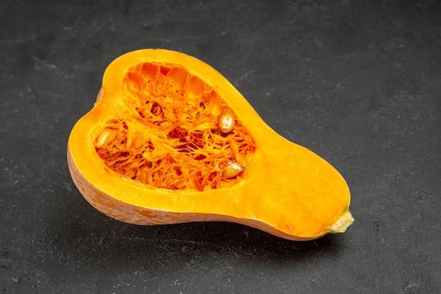 Abóbora fresca cortada de frente na mesa escura com frutas laranja foto