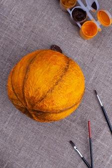 Abóbora laranja caseira feita de papel machê, pincéis, tinta sobre serapilheira, preparação e celebração do halloween