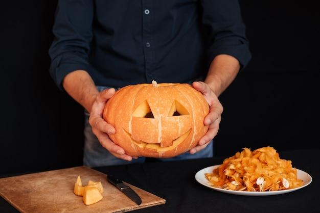 Abóbora laranja caseira para o halloween nas mãos dos homens. preparação para celebração tradicional de outono de decoração. jack's lantern
