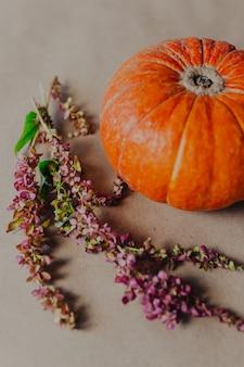 Abóbora laranja com fundo de papel kraft com flores de outono ao redor.