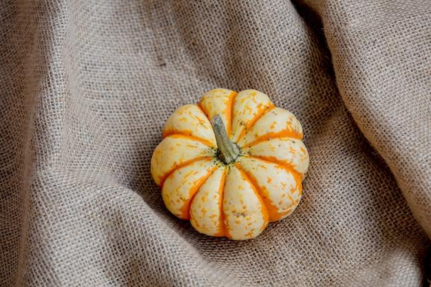 Abóbora laranja em pano de saco amarrotado.