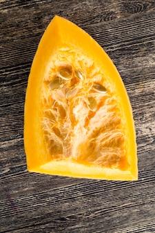 Abóbora laranja madura cortada em pedaços enquanto cozinha pratos vegetarianos