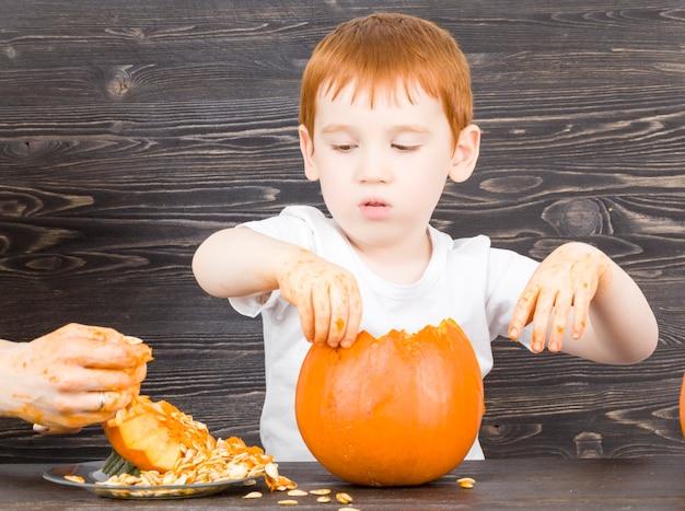 Abóbora laranja nas mãos de um menino em uma placa de madeira preta, close-up