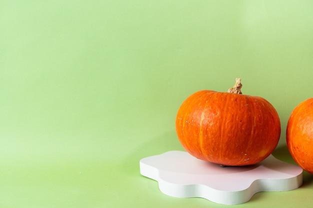 Abóbora laranja pequena sobre fundo verde com espaço de cópia. celebração do conceito de halloween ou ação de graças. pódio de cosméticos para o dia das bruxas. outono ainda vida.
