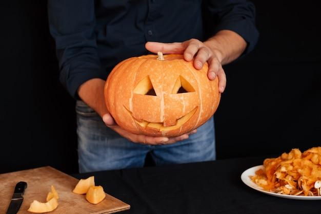 Abóbora para o halloween nas mãos dos homens