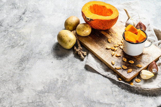 Abóbora picada na tábua rústica. ingredientes para a sopa de abóbora. abóbora picada na tábua rústica. comida saborosa e saudável. comida vegana.