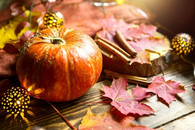 Abóbora redonda natural laranja em uma mesa de madeira com folhas caídas de bordo amarelo e vermelho, paus de canela. guirlandas de luzes, atmosfera quente de outono, ação de graças, festival da colheita, halloween. copie o espaço