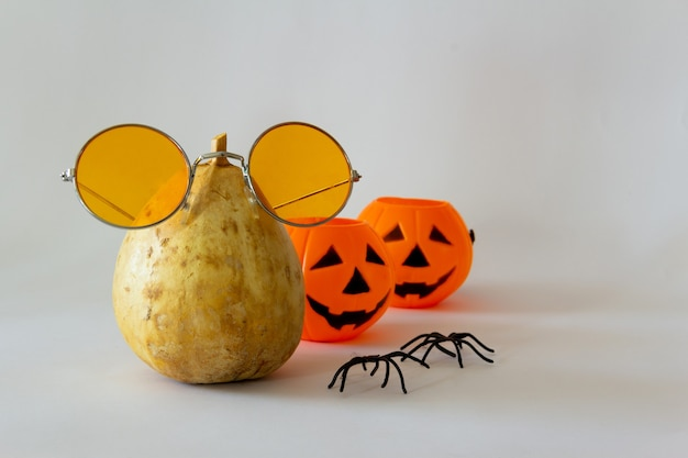 Abóbora seca fantasiada com óculos escuros e abóboras de halloween de brinquedo copie o espaço