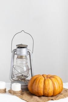 Abóbora, velas e lanterna em uma mesa de madeira branca.