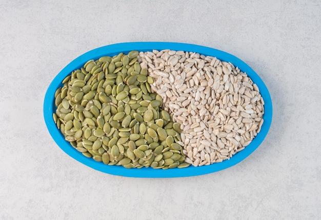 Abóbora verde e sementes de girassol em uma bandeja.