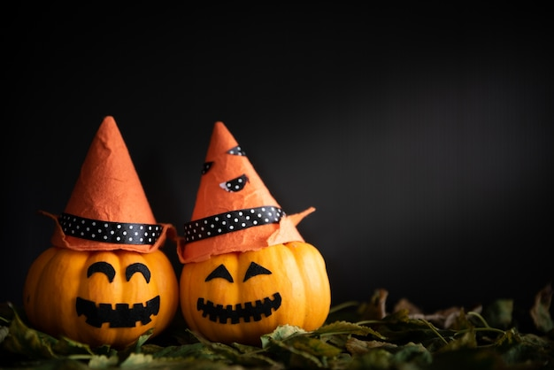 Abóboras amarelas do fantasma com o chapéu da bruxa no quarto escuro.