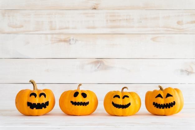 Abóboras amarelas do fantasma no fundo branco da placa de madeira com bastão. conceito de halloween