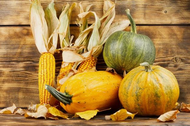 Abóboras amarelas e verdes com milho em uma mesa de madeira. conceito de colheita de outono. outono ainda vida.