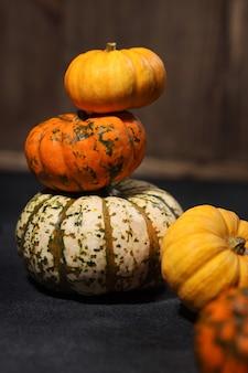 Abóboras balançando verticalmente na mesa, muitas pequenas abóboras de cores diferentes, conceito do dia de ação de graças ou símbolos do halloween