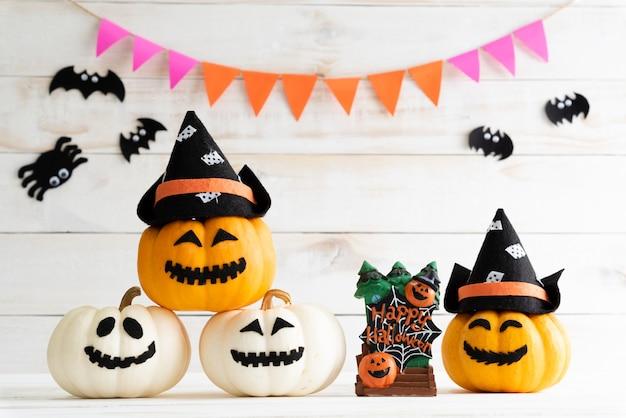 Abóboras brancas e amarelas do fantasma com o chapéu da bruxa no fundo branco da placa de madeira com bastão.