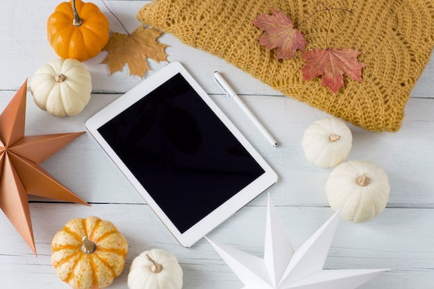 Abóboras brancas e laranja, um cobertor laranja de malha, decoração, folhas de outono, uma caneta e um tablet