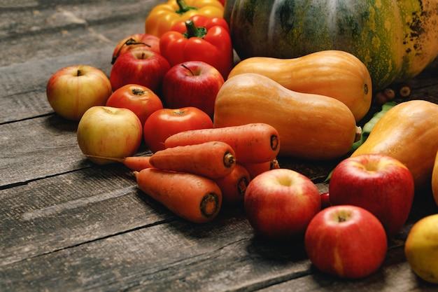 Abóboras, cenouras e maçãs vermelhas na mesa de madeira