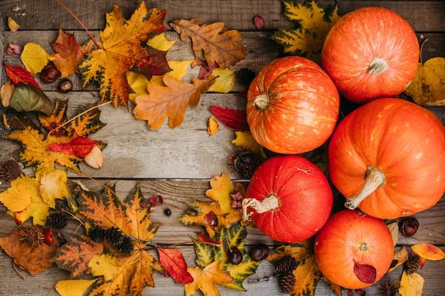 Abóboras com folhas de outono, mesa de madeira. abóboras de halloween laranja na composição de outono.