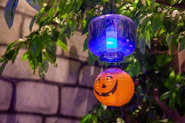Abóboras com luzes decoradas nas árvores em uma festa de halloween.