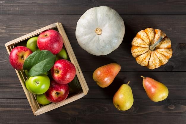 Abóboras com maçãs maduras em uma caixa e peras no escuro de madeira.