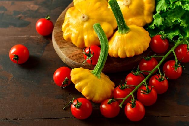 Abóboras com tomate cereja e salada em uma mesa de madeira