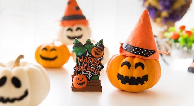 Abóboras de fantasma brancas e amarelas com chapéu de bruxa e texto de feliz dia das bruxas em borad.