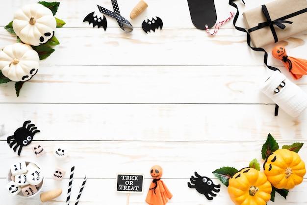 Abóboras de fantasma branco e amarelo com artesanato de halloween em fundo branco de madeira