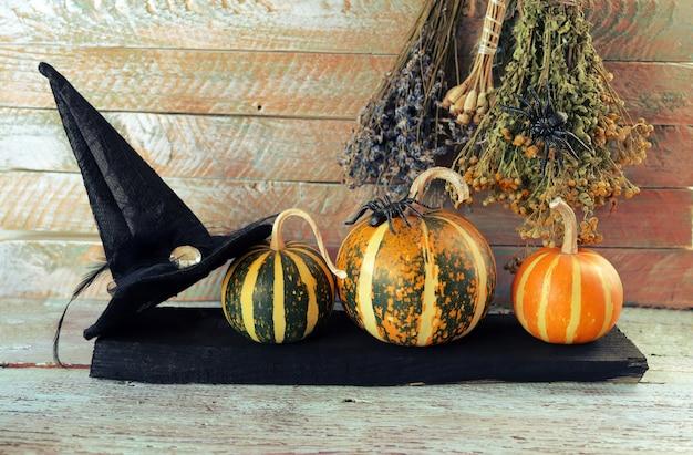 Abóboras de halloween com chapéu de bruxa, aranhas e buquês de ervas secas em uma mesa de madeira