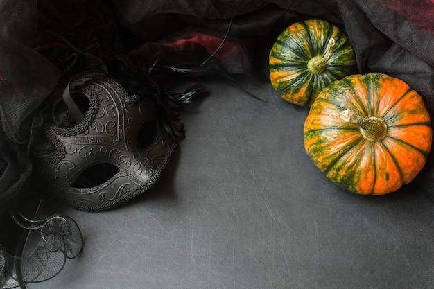 Abóboras de halloween e máscara de baile de máscaras em fundo cinza simulando conceito de feliz dia de ação de graças