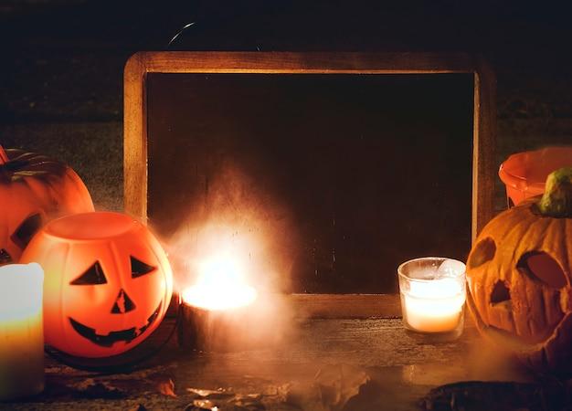 Abóboras de halloween e velas com quadro-negro