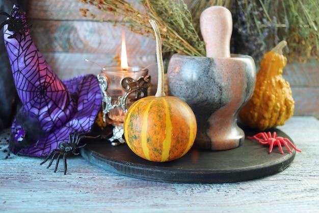 Abóboras de halloween em uma mesa de madeira uma lanterna com um fogo aceso um chapéu de bruxa aranhas