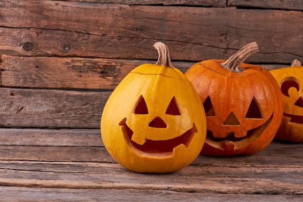 Abóboras de halloween engraçadas em fundo rústico.
