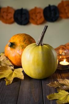 Abóboras de halloween na mesa de madeira com vela e folhas de outono amarelas