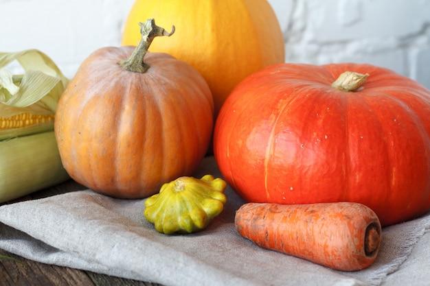 Abóboras de outono close-up e outros legumes em uma mesa de ação de graças de madeira