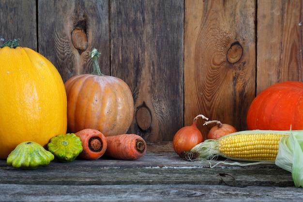Abóboras de outono e outros vegetais em uma mesa de ação de graças de madeira, foco seletivo
