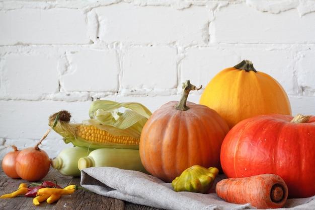 Abóboras de outono e outros vegetais em uma mesa de ação de graças de madeira