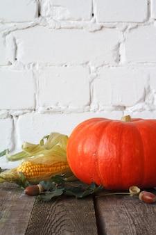 Abóboras de outono e outros vegetais em uma mesa de madeira, pano de fundo de tijolo branco