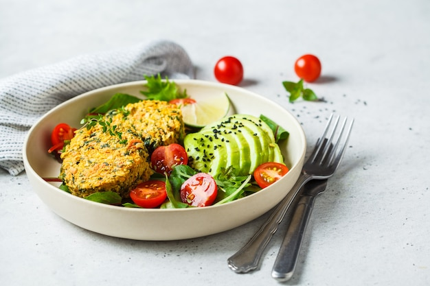 Abóboras do vegetariano e do quinoa do vegetariano com salada em uma placa branca.