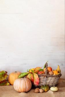 Abóboras e cesta de frutas de outono na mesa de madeira contra um fundo branco de madeira