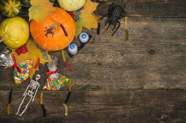 Abóboras e doces em uma velha mesa de madeira com aranhas e esqueleto