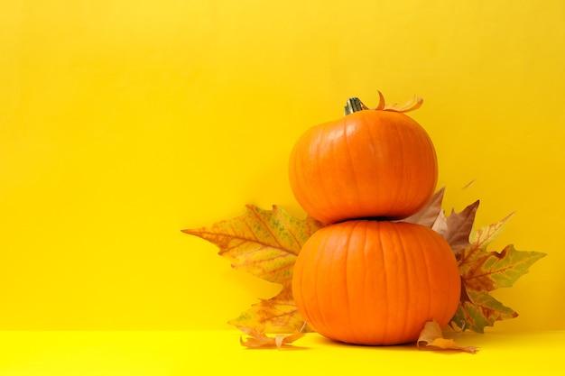 Abóboras e folhas de outono em fundo amarelo