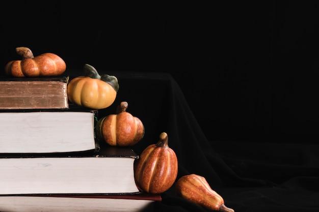 Abóboras e livros sobre fundo preto