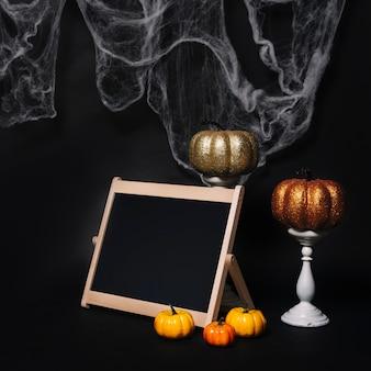 Abóboras e lousa perto de decorações de halloween